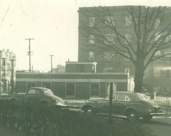 Cars Parked on City Street Brick Buildings Stop Sign Corner Vintage Black White Photo Photograph
