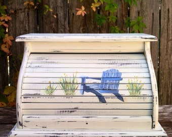 Bread box in distressed antique white with blue beach chair hand painted on front of roll top door