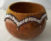 Medium brown gourd bowl, fancy beaded rim with brass bells. 944.
