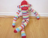 Candy striped sock monkey plush with red, blue, yellow, and purple stripes