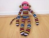 Striped sock monkey plush doll - black, magenta, orange, red, and blue with goofy face