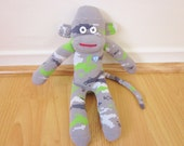 Gray, white, and green camouflage sock monkey plush in a pixelated or digital pattern