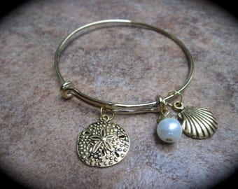 Beach theme adjustable wire bangle bracelet with Sand dollar pearl and shell charms Gold finish Summer bracelet Beach bracelet