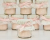 1 mini 2 oz. mason jar filled with pink  lemonade dressed with white lace, white fabric and pink bow! So cute for a winter baby shower!