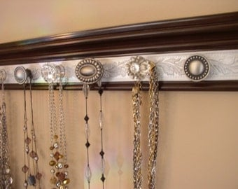 "Brown with silver embossed area. This necklace rack gives you beautiful decor & Jewelry storage w/ 7 decorative cabinet knobs  20"" long"