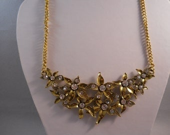 Gold Tone Bib Necklace with Leaf and Rhinestone Pendant Beads on a Gold Tone Chain