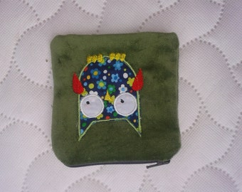 A coin purse in green velvet with an owl on the front