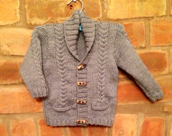 Grey cable knit cardigan with wooden toggles and pocket detail avaloable in 0-6 months, 6-12 months and 1-2 years