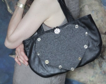 Small, over your shoulder, black leather and grey wool bag with heart pocket.