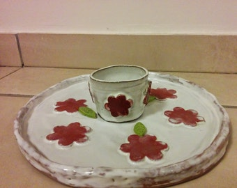 A clay handmade white serving plate with a dipping glass