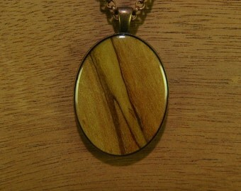 Spalted Maple wood, resin encased in antique bronze finish pendant bezel with chain