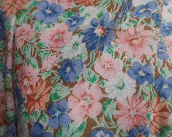 Floral knit fabric pale colors with a brown background