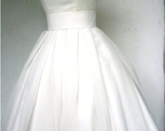 A beautiful ivory wedding dress with a boat neckline. Made from chiffon with a darling tea length skirt which is pleated. DM49-8