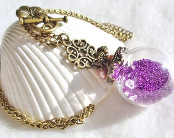 Round glass orb necklace filled with delicate purple fiber beads, hearts and bronze chain