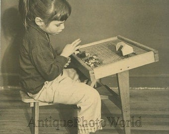 Cute girl playing with wooden toy blocks antique photo