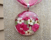 1.5 inch flower cabochon. Hot pink/soft cream pressed blooms underglass.