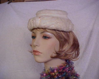 White faux fur hat with sequins in a  design and back bow- no label- fits 21 to 21 1/2 inches