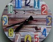 Unique wall clock. Face looks like wood slats. Numbers look like license plates.