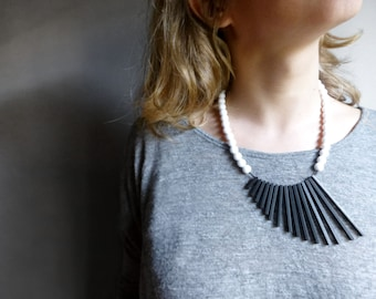 minimalist geometric necklace with black sticks and white beads , contemporary jewelry