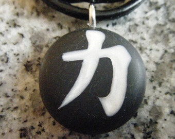 """Japanese kanji symbol for """"STRENGTH"""" hand carved on a polymer clay black color background. Pendant comes with a FREE necklace"""