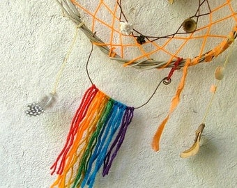 Rainbow kiss magical dream catcher weaved in orange and brown yarn with many surprises..
