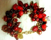 Chunky Bead Charm Bracelet in a Variety of Reds and mixed metal charms