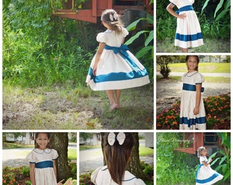 Girls custom non smocked silk dupioni dress w/striped hem, band trimmed sleeves, and a peter pan collar. Two colors of choice. Free bow.