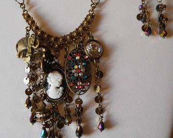 Steampunk  Necklace with a Boho influence. Black and white cameo, selected charms,brass drop chain,Swarovski rivoli,and assorted crystal.