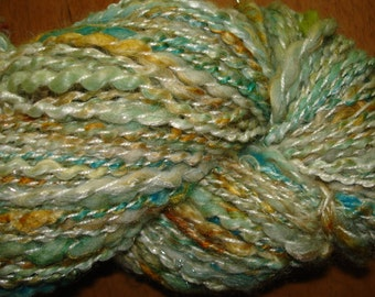 Handspun Yarn. Merino, Silk, and mixed fibers. Bulky weight Yarn,White with Gold, Greens, and Turquoise. 175 yards.