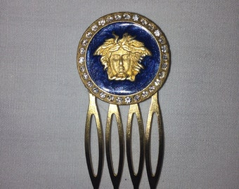Blue and gold emblem hair comb surrounded by diamonds