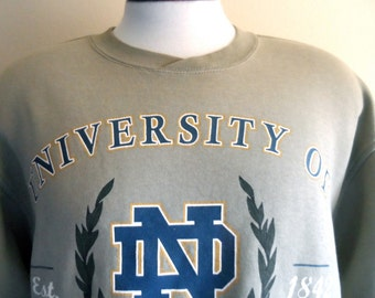 Go UND Fightin' Irish vintage 90's University of Notre Dame football graphic sweatshirt blue gold crest print beige khaki crew neck fleece