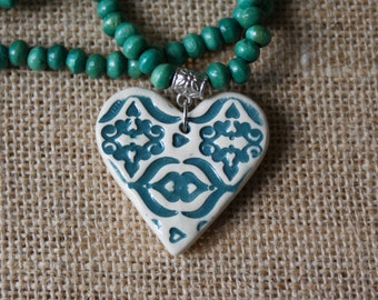 Green ceramic heart necklace with wooden beads.