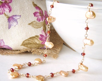 Peach keshi pearl necklace with garnets, gold jewelry