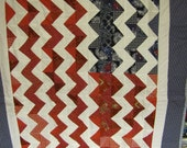 Red, White, and Blue throw with chevron patterned stripes on the front.  The back of the quilt is bright red fleece.