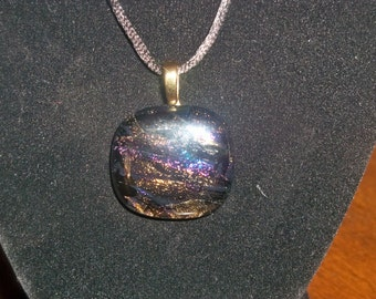 """Dichroic glass necklace black blackground with purple, gold and amber hues 30mm x 30mm.  Comes with 16"""" black satin cord."""