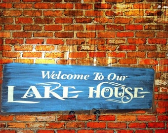 Welcome your guests with this 6 x 24 in Welcome to Lake House Painted Wood Sign.