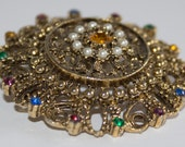 Lovely carved metal and colored stone pin. Costume jewelry from the 40's.