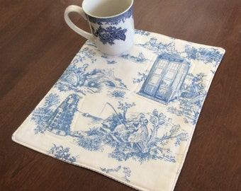 Dr. Who mug rug.Elegant toile de jouy blue, featuring Tardis and a Dalek. 12 by 10 inches.