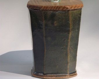 An unusual 8 sided green-gray one of a kind ceramic vessel, with a custom fitted 2 piece oak lid & a light green glass knob.
