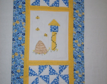 "wall hanging, embellished with :bee buttons"". sleeve for hanging in back"