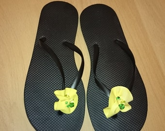 black flip flops with yellow flower