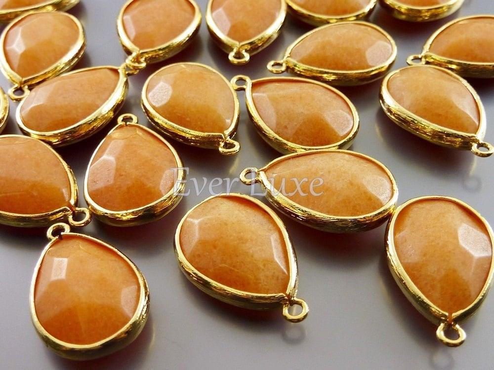 2 apricot color synthetic jade stone in gold bezel frame. Black Bedroom Furniture Sets. Home Design Ideas