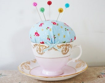 floral teacup pincushion with floral shaped pins.