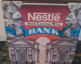 60's Nestle Hot Cocoa Mix Piggy Bank Collectible Tin by The Nestle Company, Inc.