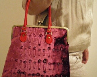 Safety pin design hand printed fuschia kiss lock handbag with red leather handles