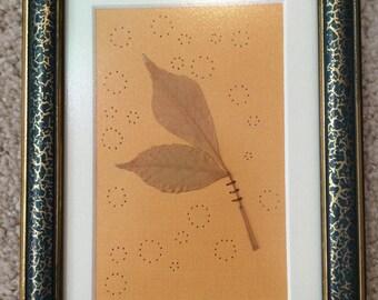 Yellow ornately framed leaf art