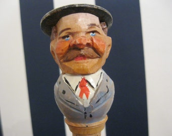 """Carved wooden head on a cork bottle stopper who doffs his hat & reveals his """"date"""""""