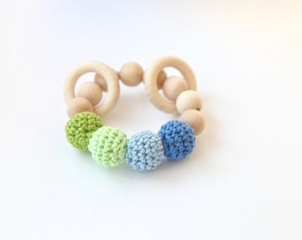 Rattle toy for baby, small teething ring in pastel colors. Wooden teether in light green, blue.