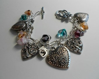 Natural stones and metal hearts on a bracelet with a sweet flower clasp.