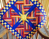 Fiesta Sunburst quilted wall hanging - bright reds, yellows, greens and blues highlight the geometric patterns.